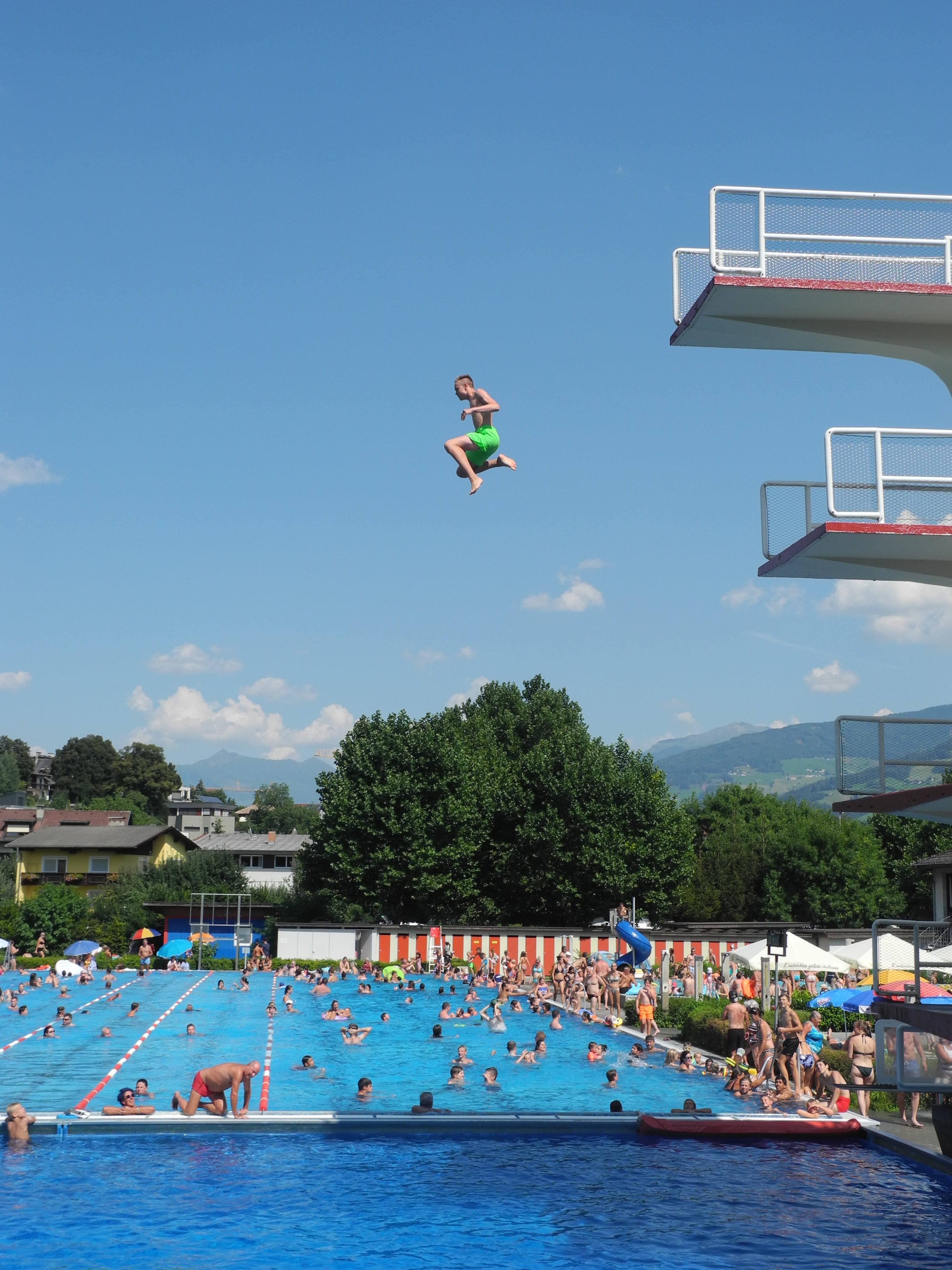 Kind springt vom Turm im Freibad Schwimmbad